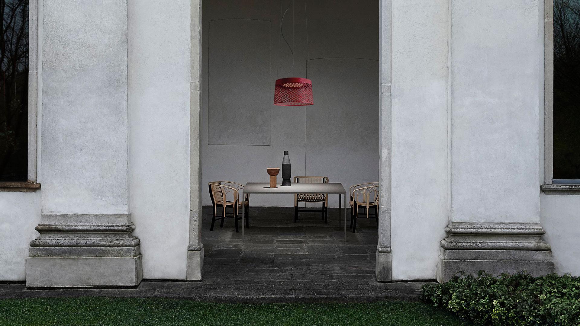 Lampada a sospensione outdoor Twiggy Grid creata dal designer Marc Sadler per Foscarini appesa sopra un tavolo in un contesto esterno durante il giorno